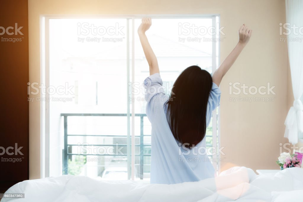 Asian woman sitting near window while stretching on bed after waking up with sunrise at morning, back view stock photo