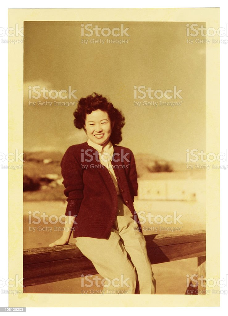 Asian Woman Sitting on a Railing stock photo