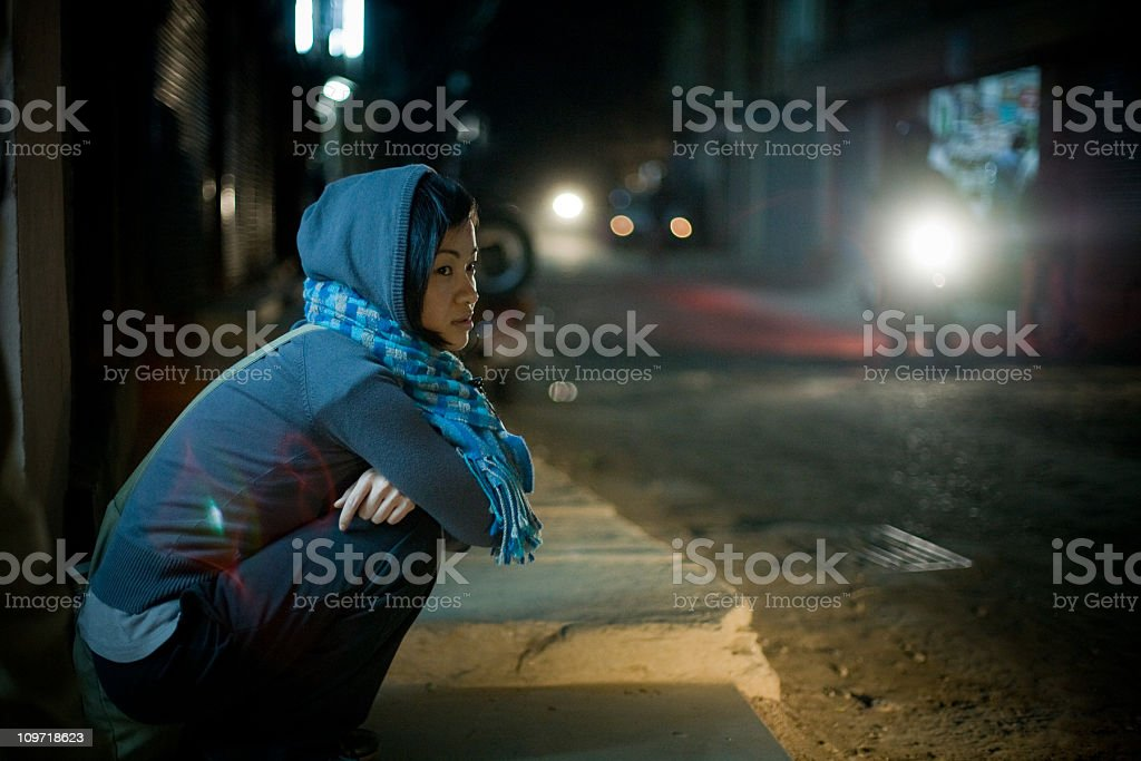 Asian woman sitting on street at night royalty-free stock photo