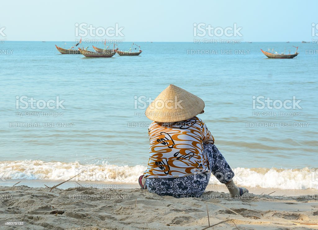 Asian woman sitting on the beach stock photo