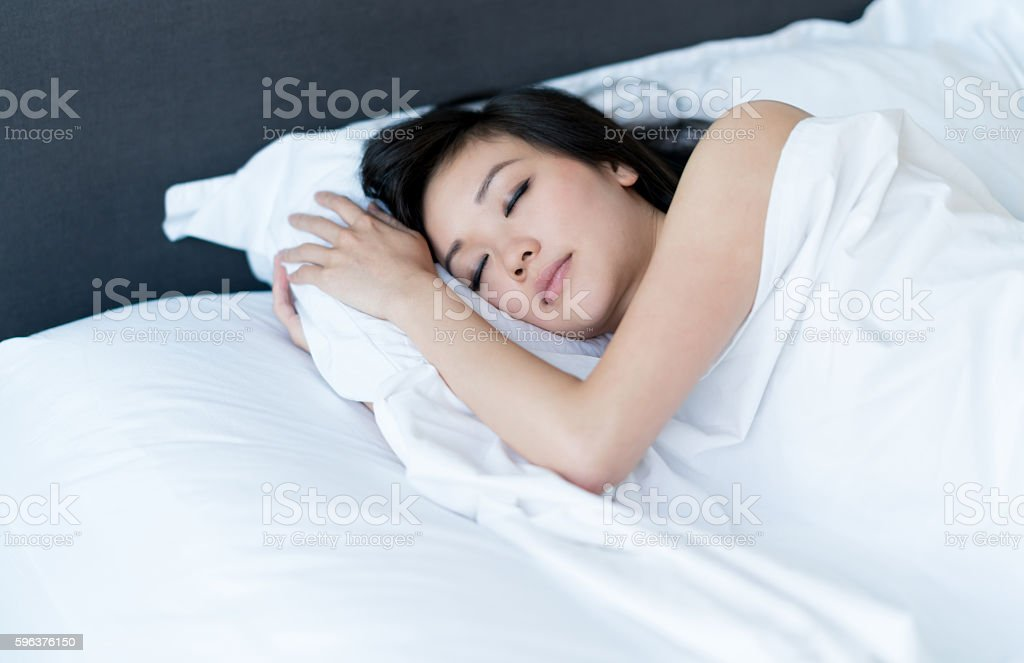 Asian woman sleeping in bed at home stock photo