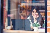 Asian woman smile while working with laptop