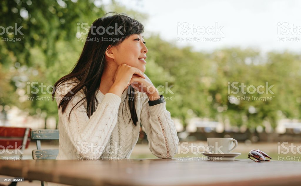 Asian woman spending free time at outdoor cafe stock photo