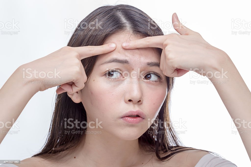 Asian woman squeezing spot on forehead stock photo