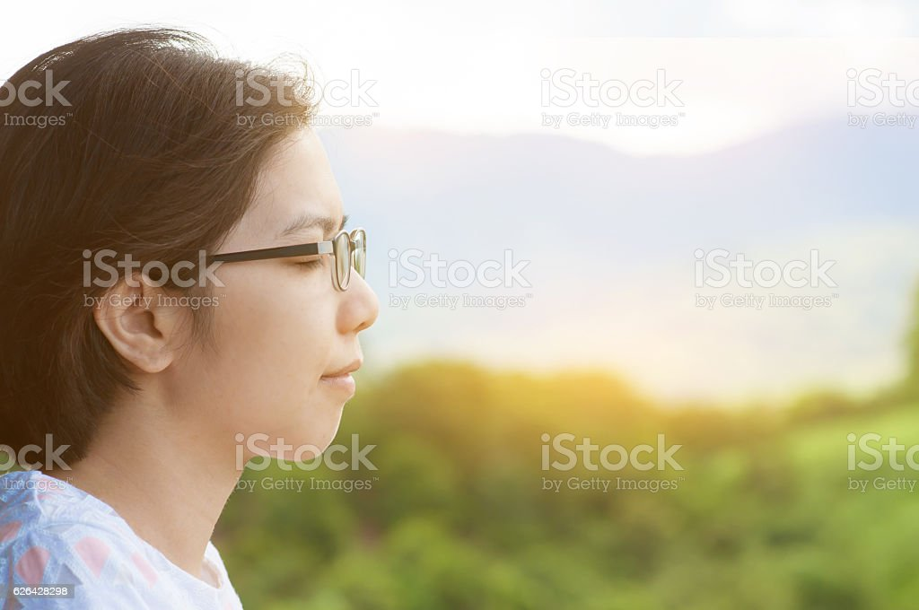 Asian woman standing at balcony and breathing fresh air. stock photo