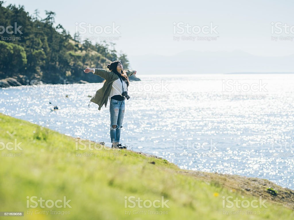 asian woman standing at cliff with camera stock photo