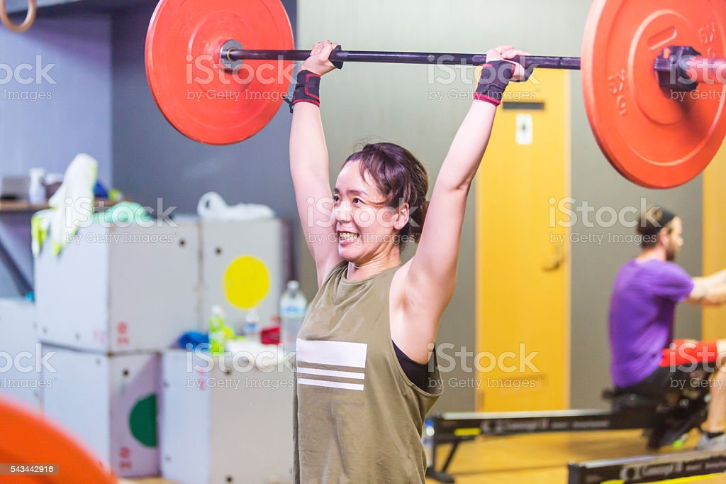 Asian Woman Straining While Weightlifting in Cross Training Gym Workout stock photo