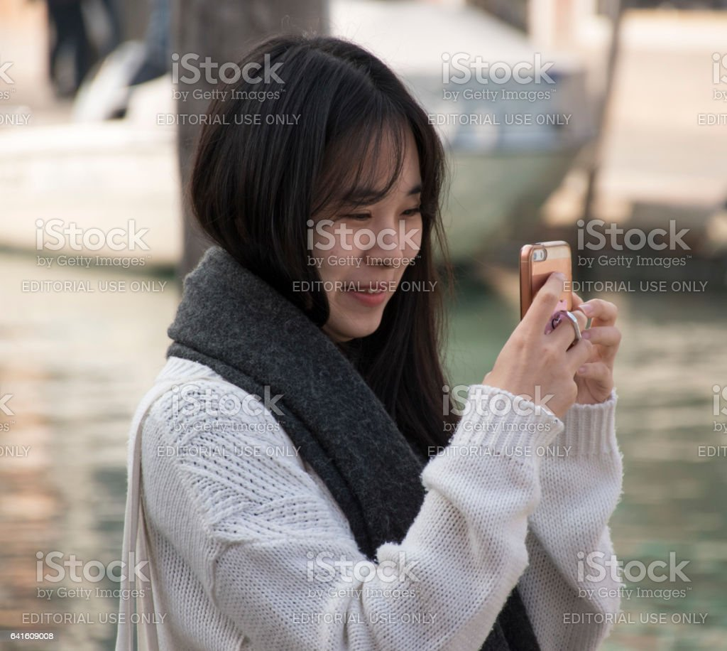 Asian woman takes selfie by canal in Muranao. stock photo