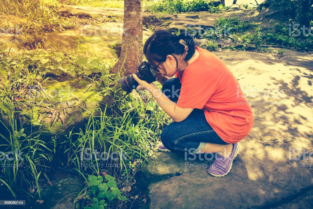 Asian woman taking with moss covered rocks. Outdoors. stock photo