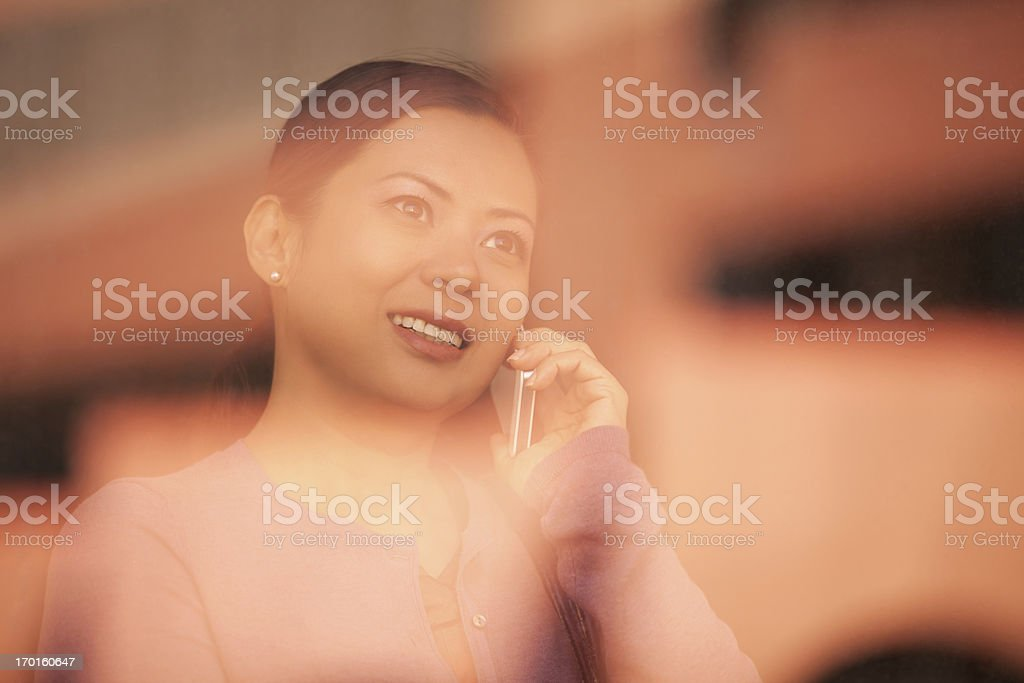 Asian Woman Talking on Smart Phone behind a Window royalty-free stock photo