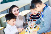 asian woman teacher and primary student do experiment in classroom