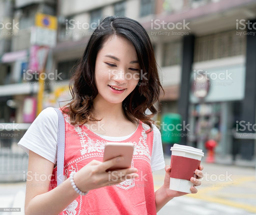 Asian woman texting and having coffee stock photo
