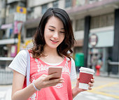Asian woman texting and having coffee