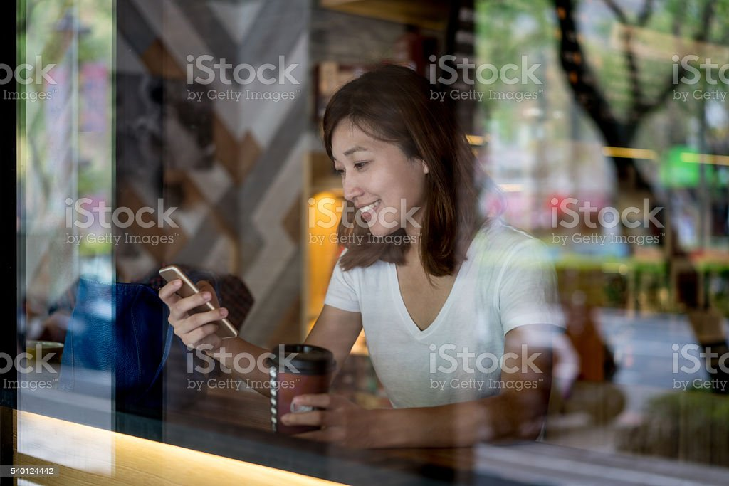 Asian woman texting on her phone at a cafe stock photo