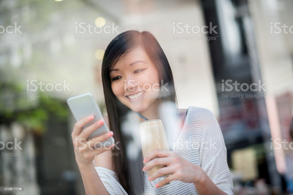 Asian woman texting while drinking a frappuccino stock photo