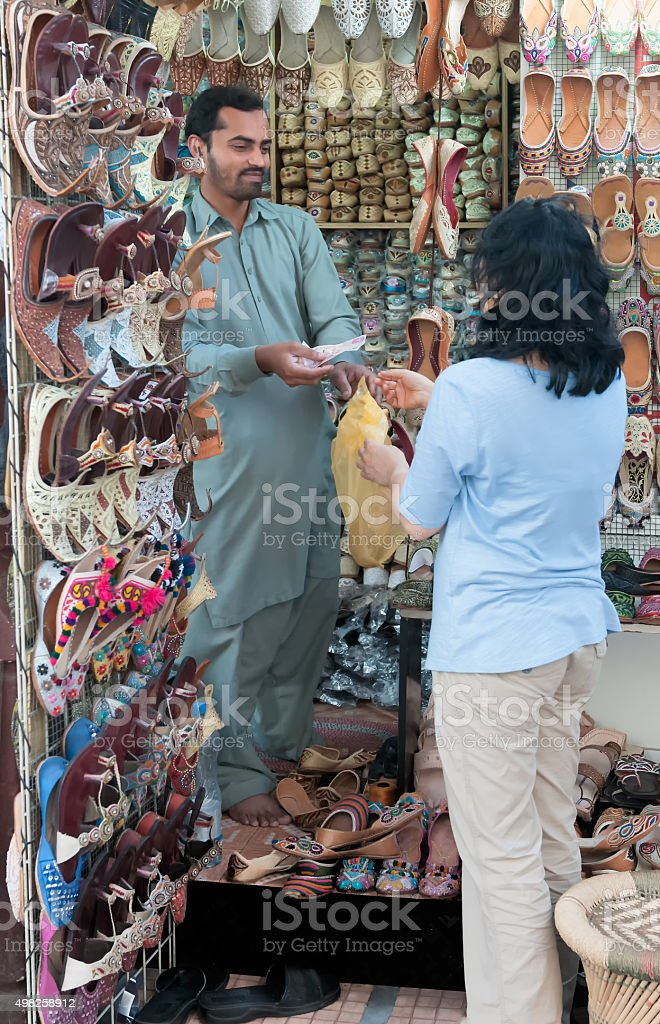 Asian Woman Tourist Paying For Shoes with Cash, Dubai, UAE stock photo