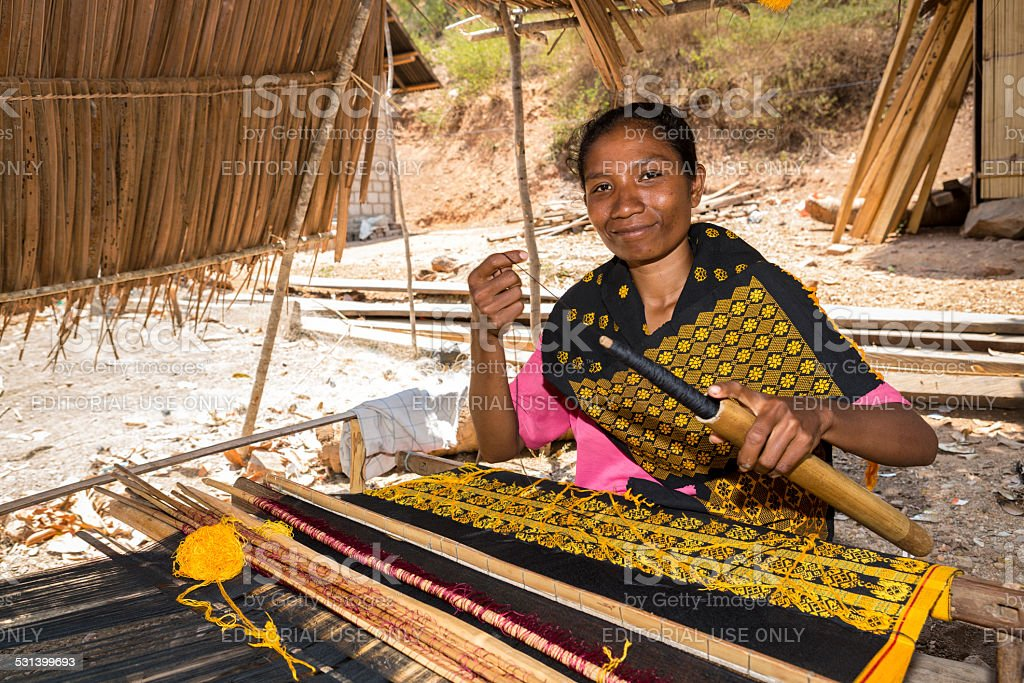 Asian woman traditionally weaving fabric stock photo