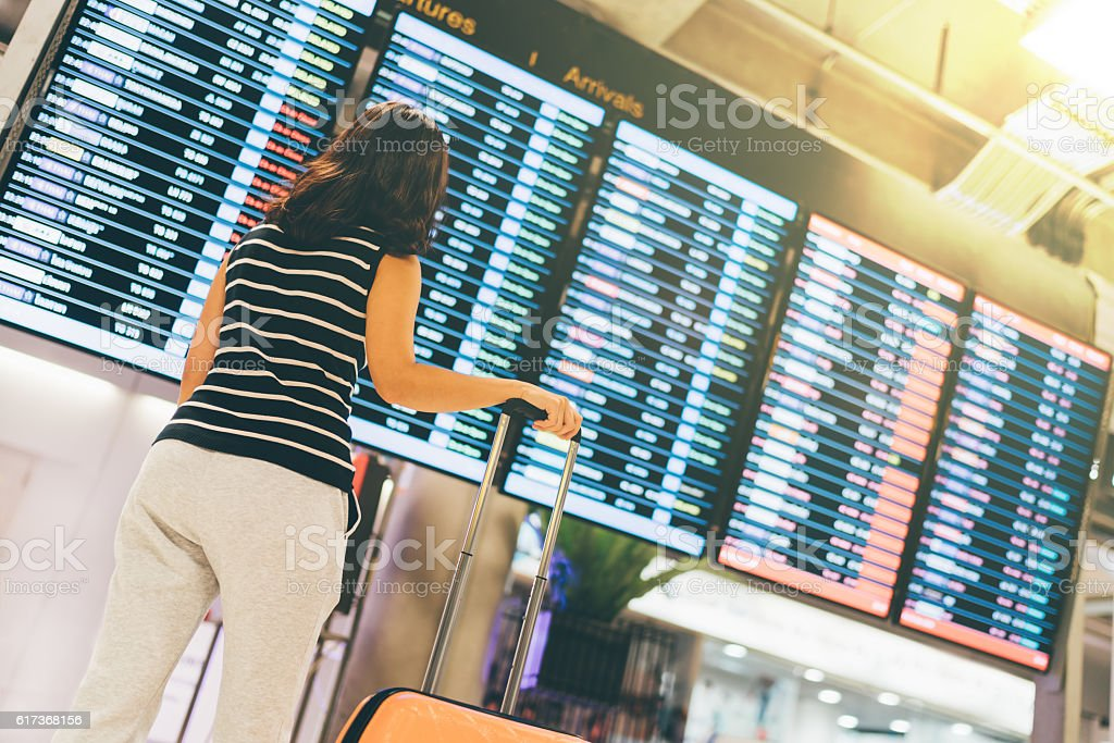 Asian woman traveler looking at flight information screen in airport stock photo