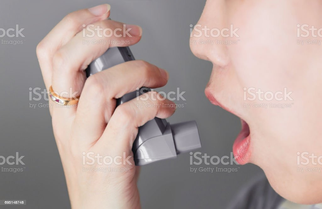 Asian woman using a pressurized cartridge inhaler extended pharynx, Bronchodilator stock photo