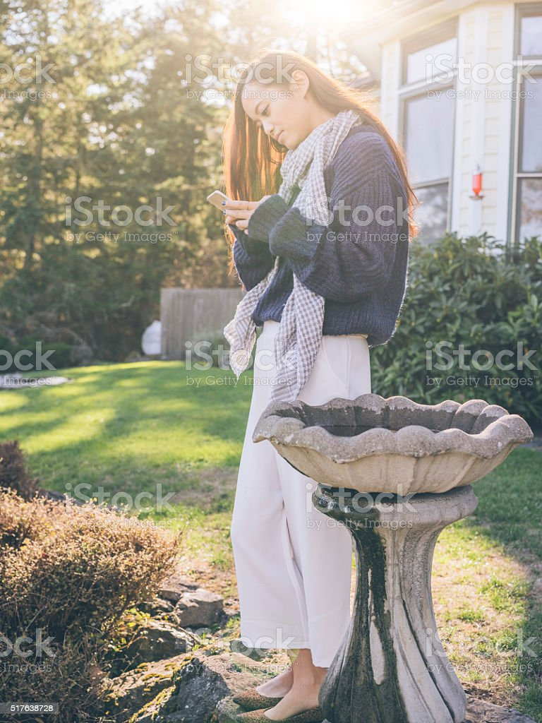 asian woman using cellphone at yard stock photo