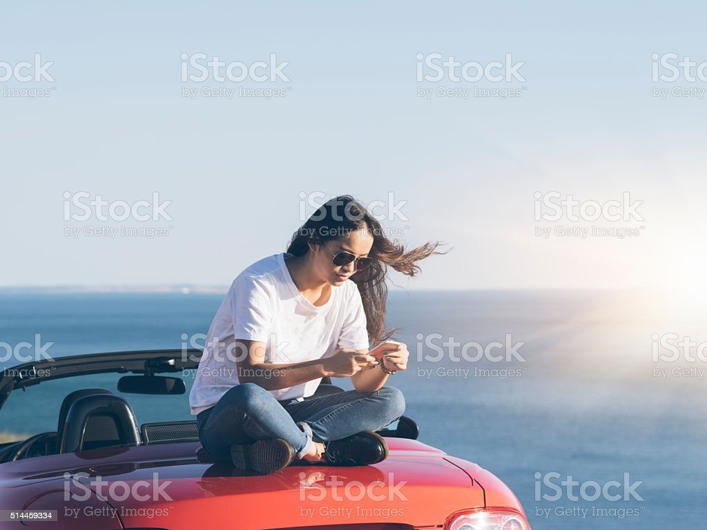 asian woman  using cellphone  on the cabriolet stock photo