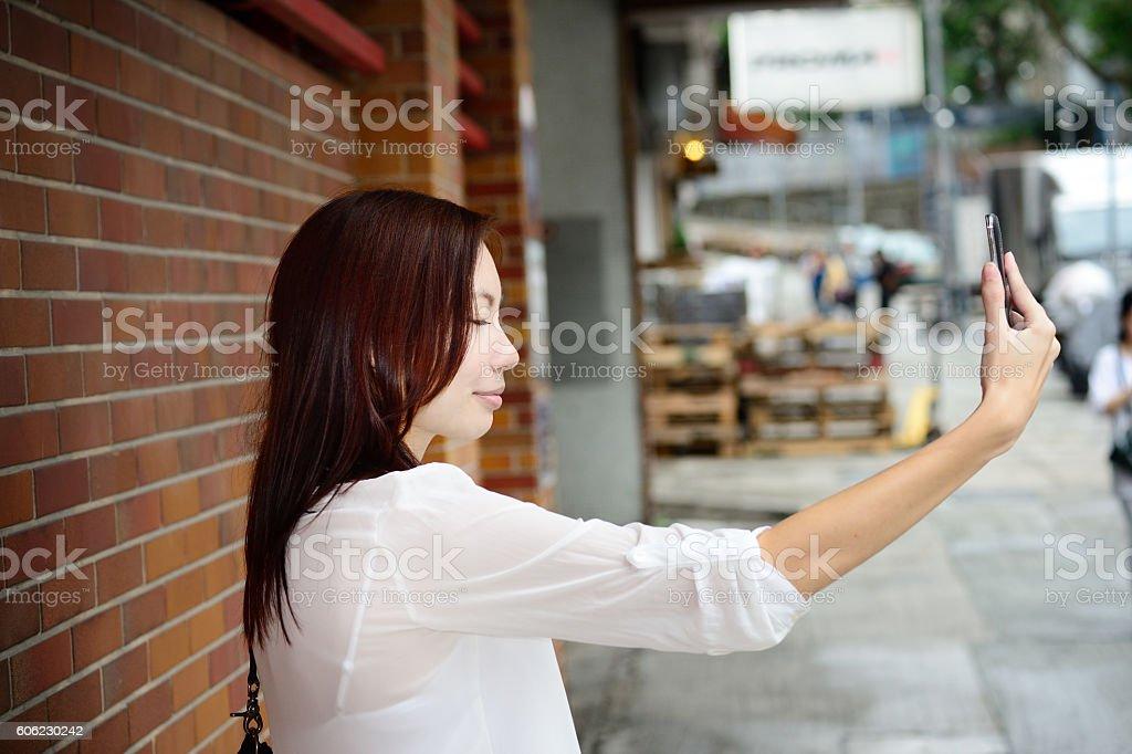 Asian woman using phone. Selfie? Closed eyes stock photo