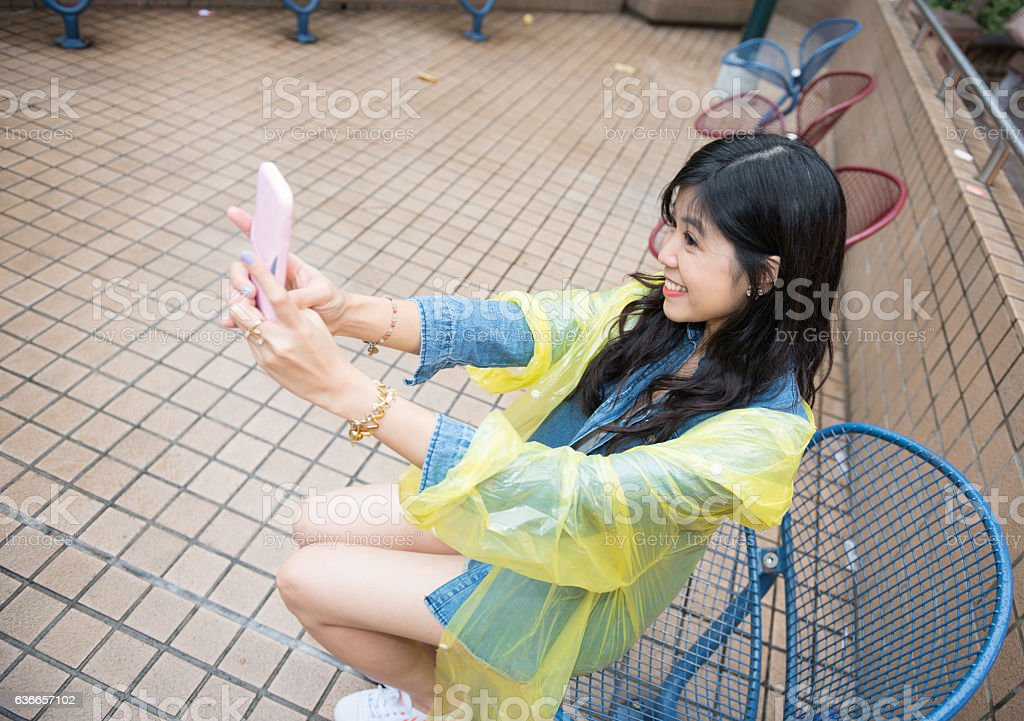 Asian woman using phone, wearing rain gear stock photo