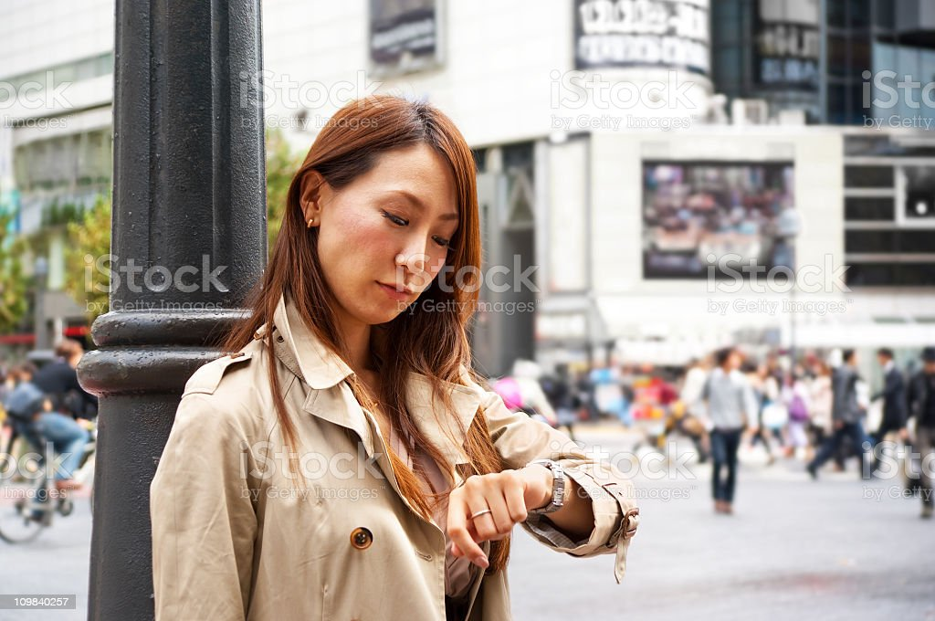 Asian woman, waiting at a busy intersection stock photo