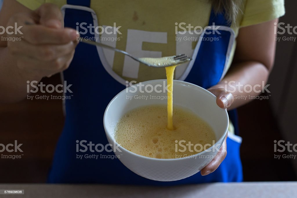 Asian woman whisking chicken egg in white bowl stock photo