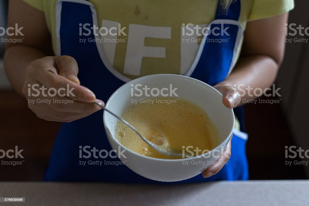Asian woman whisking egg in white bowl stock photo