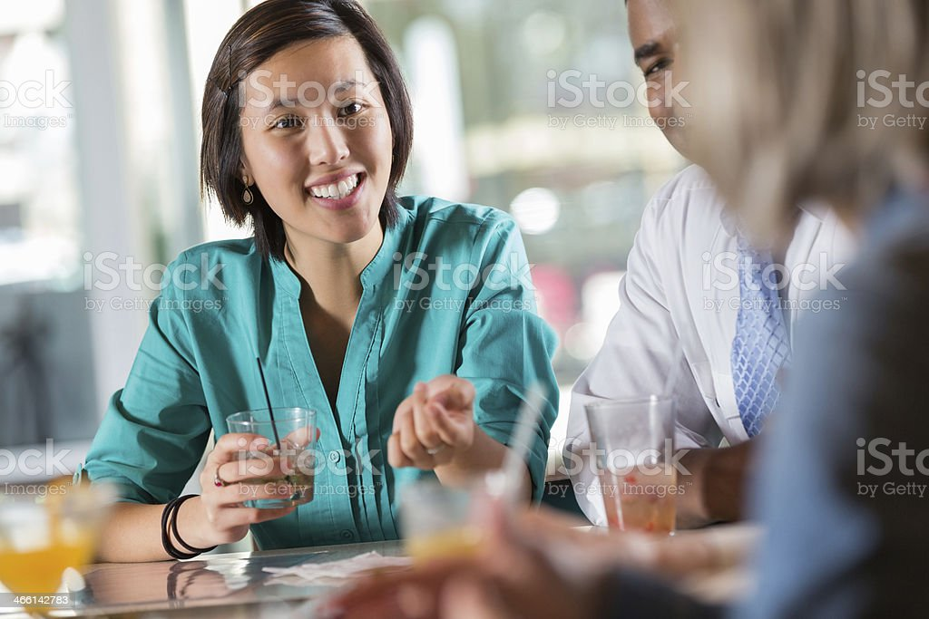 Asian woman with a group of people at a restaurant bar royalty-free stock photo