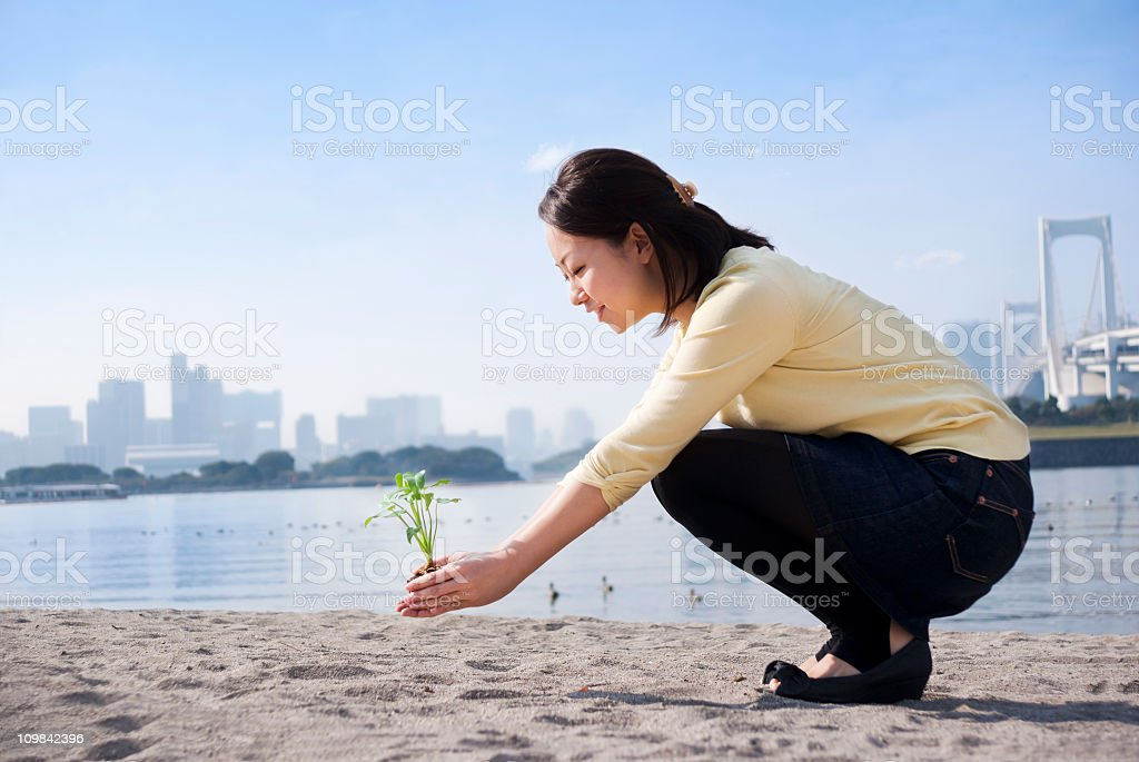 Asian woman with a seedling - Environmental conservation concept stock photo