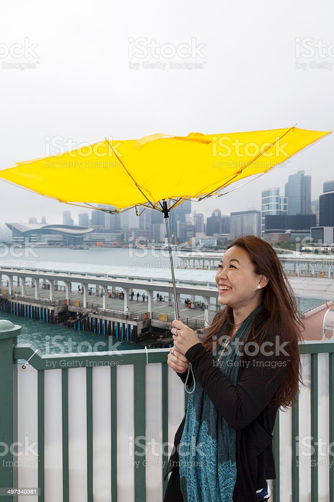 Asian woman with broken umbrella in the rain stock photo