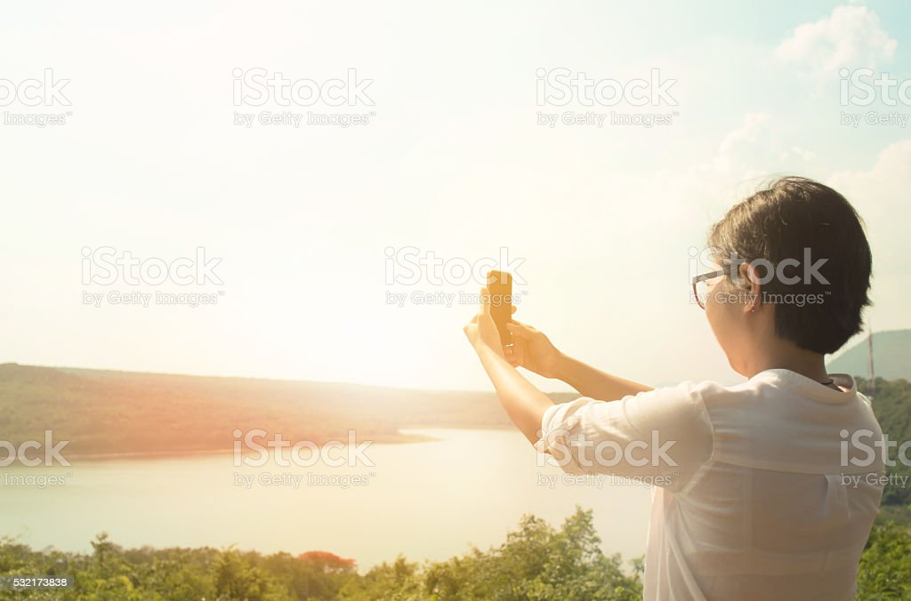 asian woman with eyeglasse taking a photo with smart stock photo