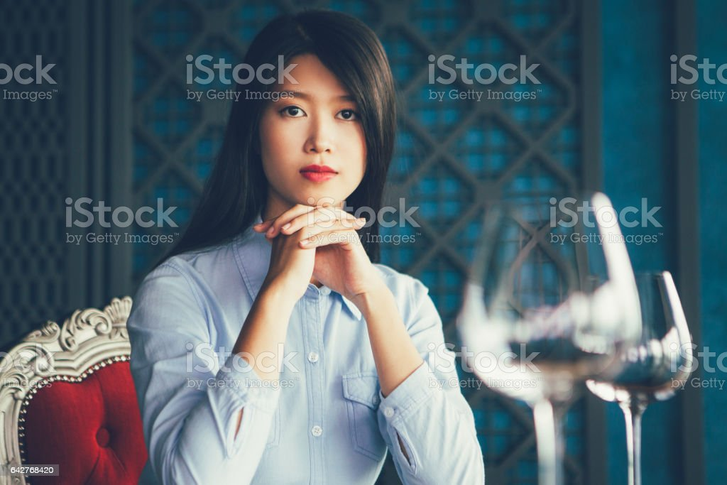 Asian Woman with Hands under Chin in Restaurant stock photo