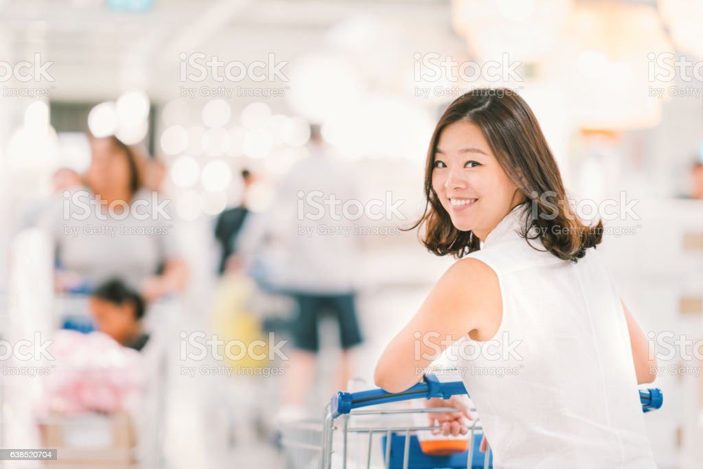 Asian woman with shopping cart at shopping mall stock photo