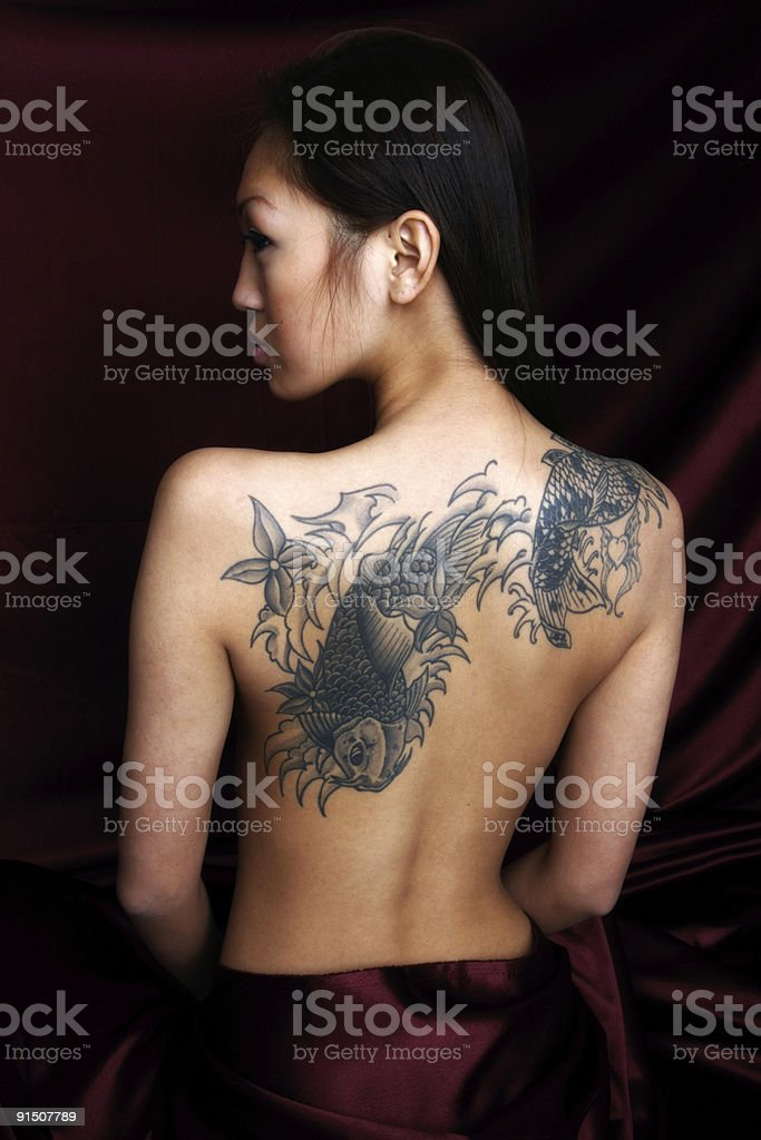 Asian woman with tattoo on her back royalty-free stock photo