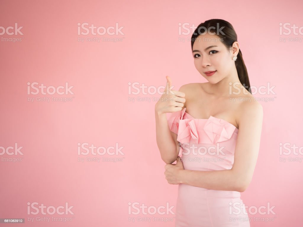 asian woman with thumb up, sexy girl show finger on pink background stock photo