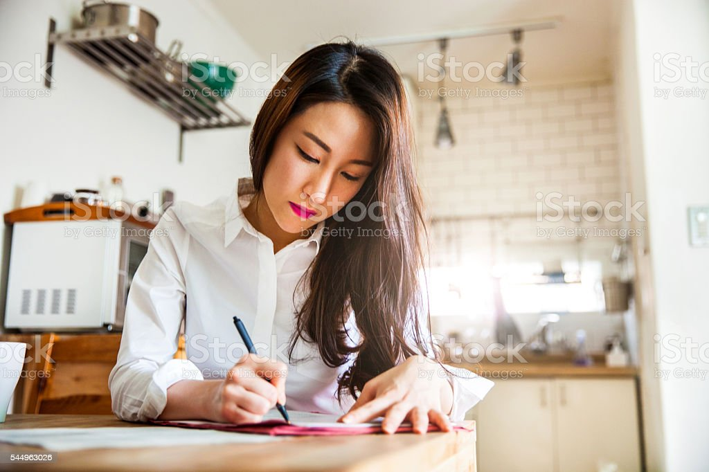 Asian woman working at home on contracts and mails stock photo