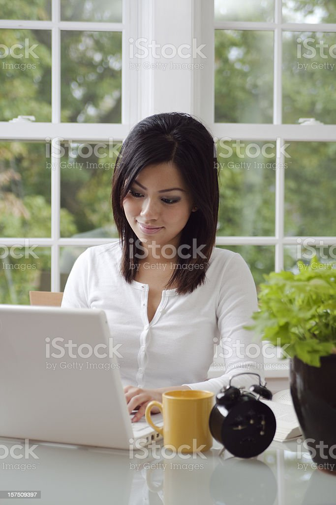 Asian Woman Working at Home, Telecommuting, Studying on Laptop Computer royalty-free stock photo