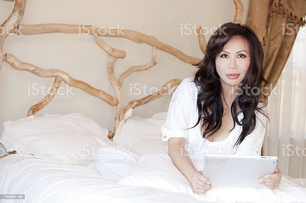 Asian woman working from home in bed holding a tablet royalty-free stock photo