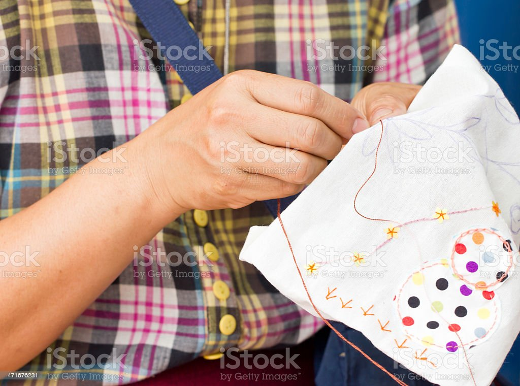 Asian woman's hand sewing. royalty-free stock photo
