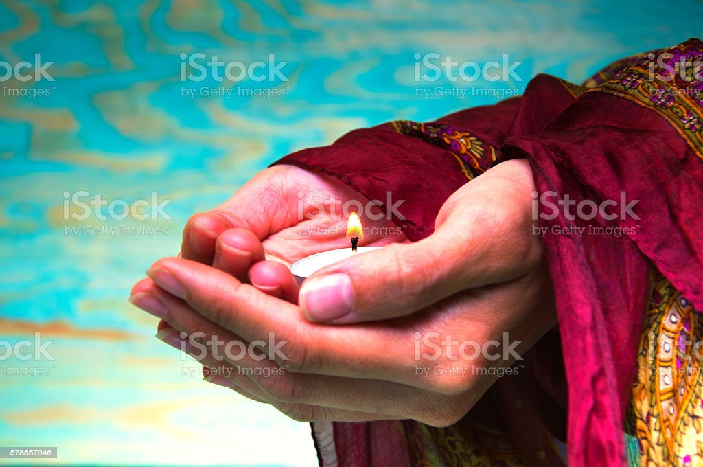 Oriental woman's hands holding a tea light candle stock photo