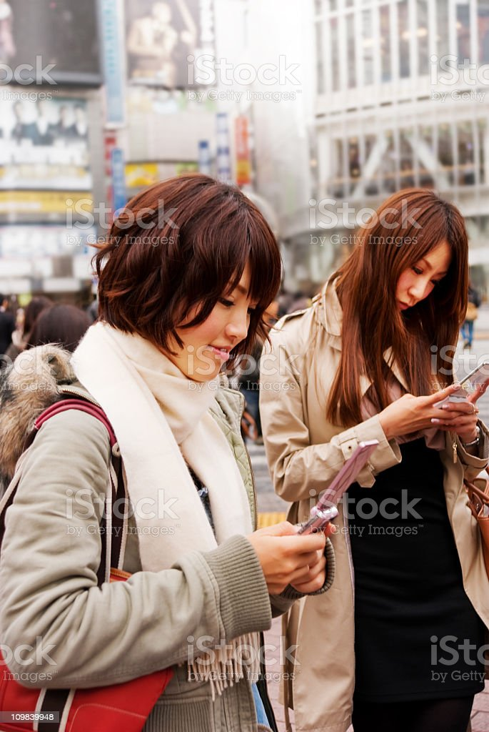 Asian women with cell phones on the street stock photo