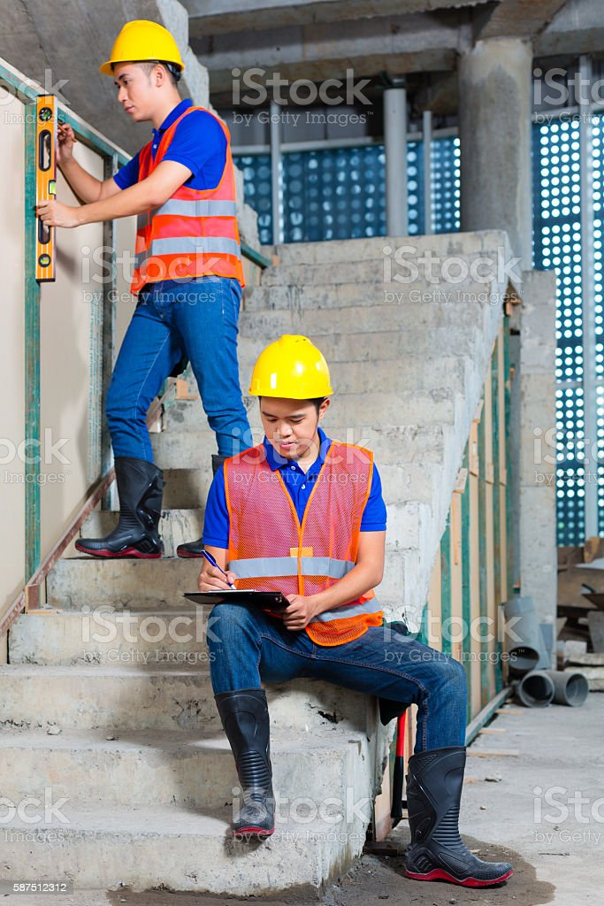 Asian workers on building or construction site walling stock photo