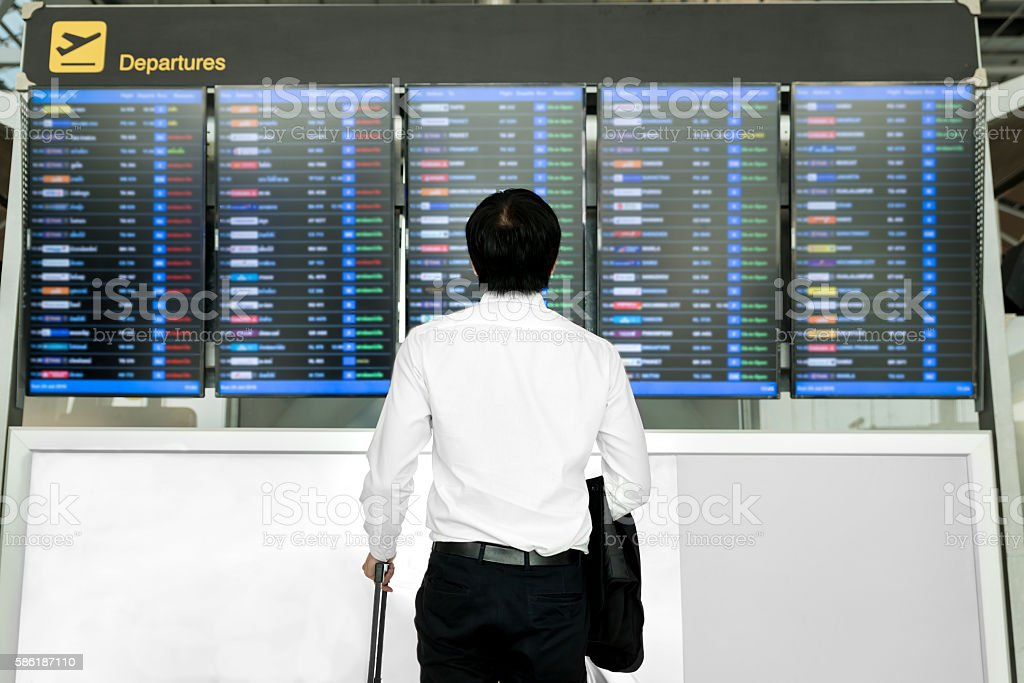 Asian young business man with luggage near flight timetable. stock photo