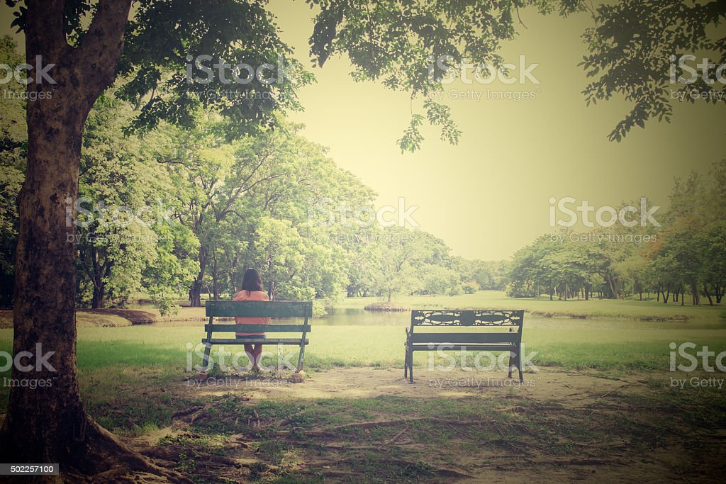 Asian young lonely woman on bench in park stock photo
