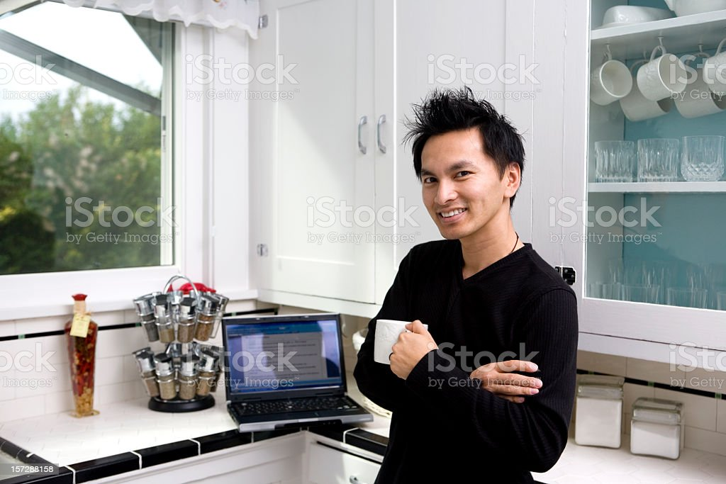 Asian Young Man Drinking Coffee in Kitchen, Using Laptop, Copyspace royalty-free stock photo