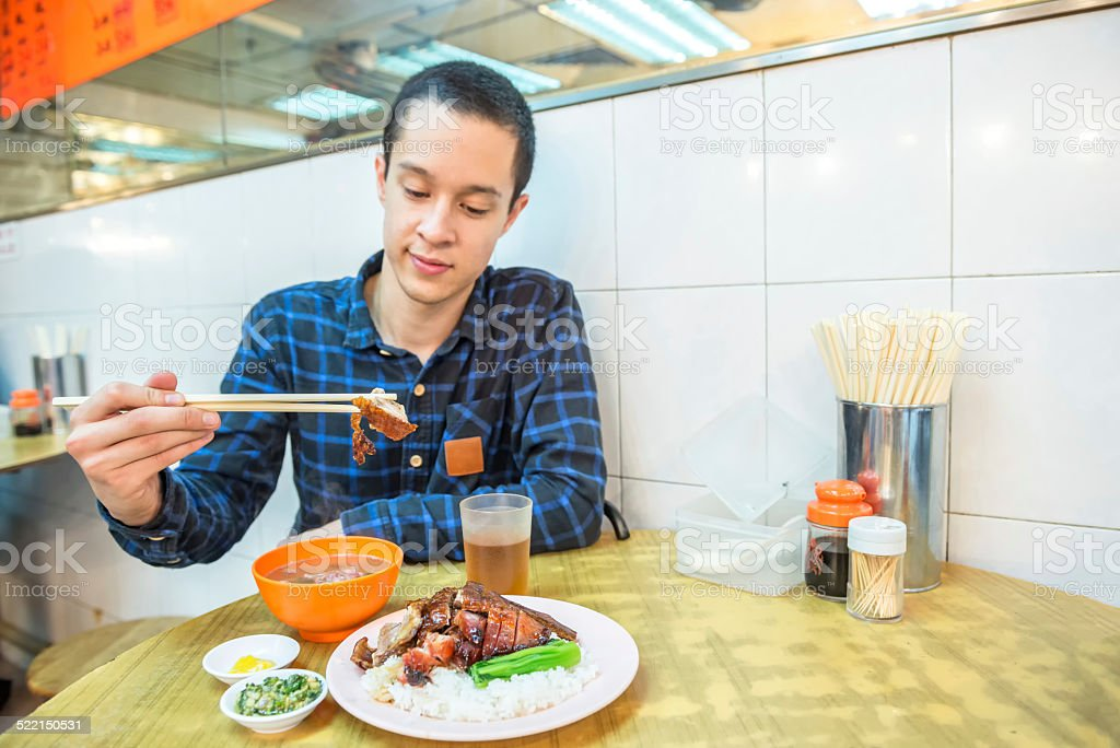 Asian Young Man Eating Dinner in a Hong Kong Caf? stock photo