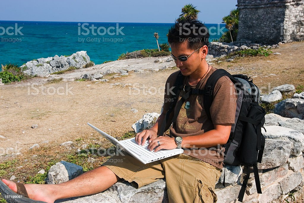 Asian Young Man Hiking in Mexico Using Laptop, Copy Space royalty-free stock photo